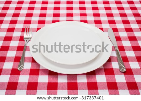 Empty white plates on red checkered tablecloth