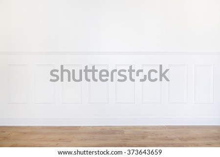 Empty white room with parquet floor and wood trimmed wall - stock photo