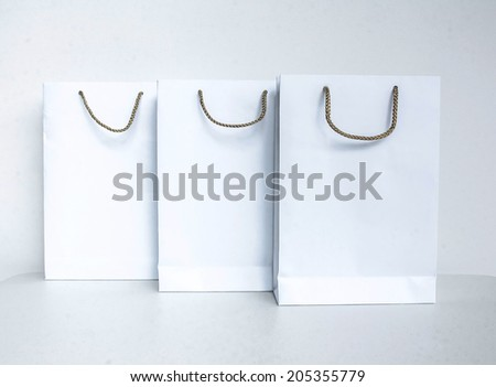 Empty white shopping bag with gray rope hanging isolated on white background
