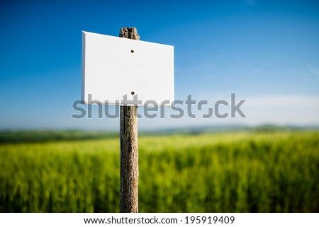 Empty white signboard with vintage wooden post and beautiful nature blurred in the background - stock photo