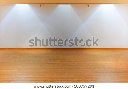 Empty white wall with spot lights and wooden floor - stock photo