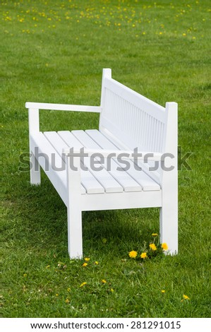 Empty white wooden bench on green grass