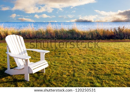 Empty white wooden chair outdoors at sunrise.  Golden early morning light in a waterside setting.