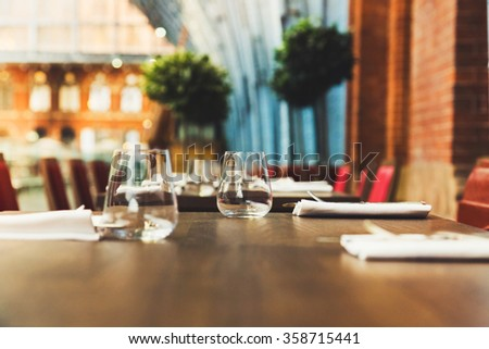 Empty wine and drink terrace with tables and chairs at King Cross London train station - stock photo