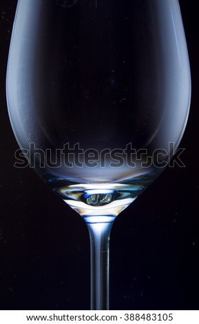 Empty wine glass against a black background