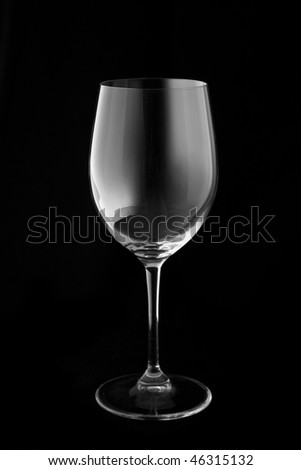 Empty wine glass against a black background.
