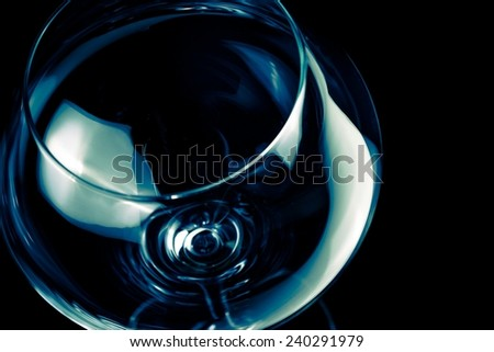 empty wine glass and light tint blue disco on black background - stock photo