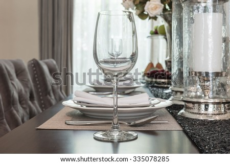 empty wine glass on wooden dinning table with table set in dinning room