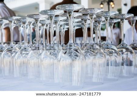 Empty wine glasses arranged in row, setup for wedding ceremony. - stock photo