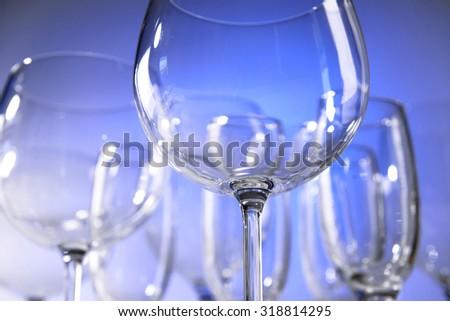 Empty wine glasses on blue background - stock photo