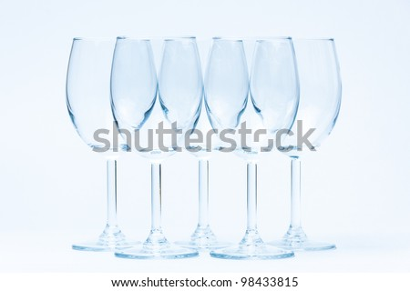 Empty wine glasses stand symmetrically on white - stock photo