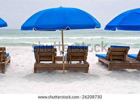 Charming Empty Wood Beach Chairs With Royal Blue Umbrellas On The Sugar White Sand  Of Panama City
