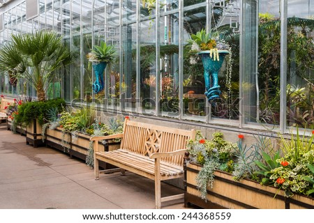 Empty wood benches along a sidewalk outside a greenhouse in a public garden - stock photo