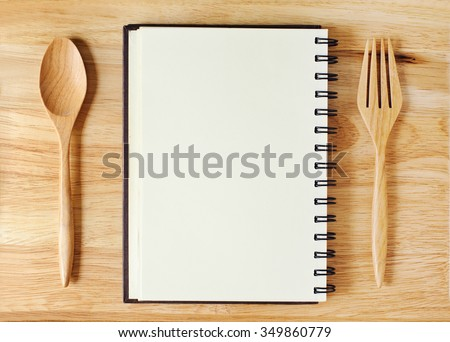 empty wood plate with notebook open and spoon ,fork - stock photo