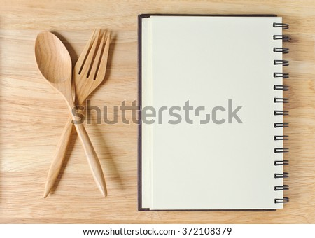 empty wood plate with notebook open and spoon ,frok - stock photo