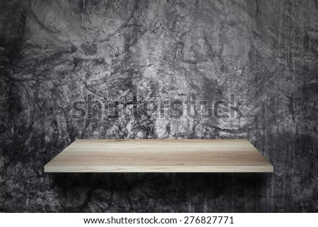 Empty wood shelf on cement wall - stock photo