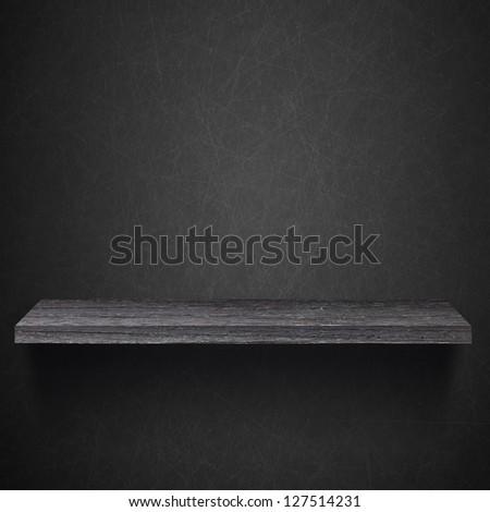 Empty wood shelf on the blackboard wall - stock photo