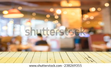 Empty wood table and blurred coffee shop  background . - stock photo