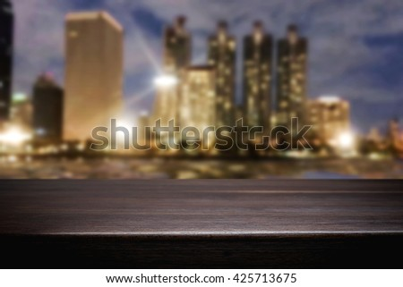 Empty wood table platform with bokeh light of night city background for product presentation display montage. - stock photo
