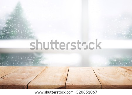 Empty Wood Table Top On Blur Window View With Pine Tree In Snow Fall Of  Morning