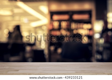 Empty Wood table top on blurred or defocus image of coffee shop of cafeteria abstract background - use for display or montage the products - stock photo