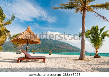 Empty wooden beach chairs on the beach with coconut trees - stock photo