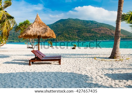 Empty wooden beach chairs with parasol on the beach with coconut tree in Phuket, Thailand with parasol on the beach with coconut tree in Phuket, Thailand - stock photo