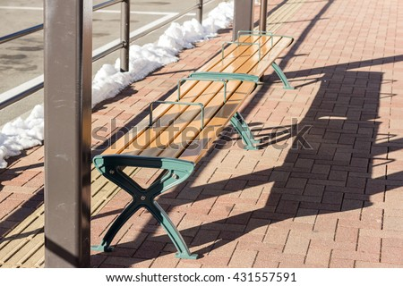 empty wooden bench at bus stop - stock photo