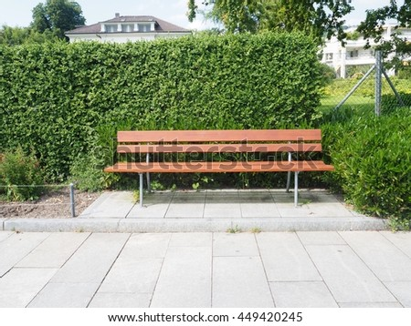 Empty wooden bench in a park  - stock photo