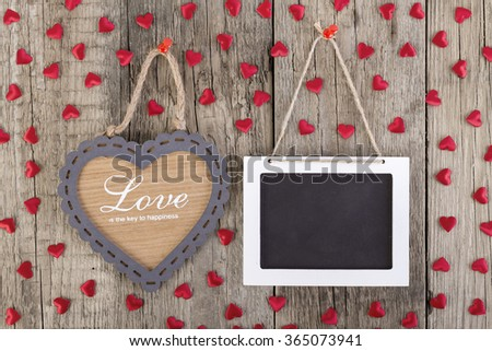 Empty wooden blackboard sign and heart shape frame with love text on wooden background. Valentines day card concept.