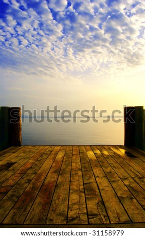 Empty wooden boardwalk on a lake with a cloudy sky