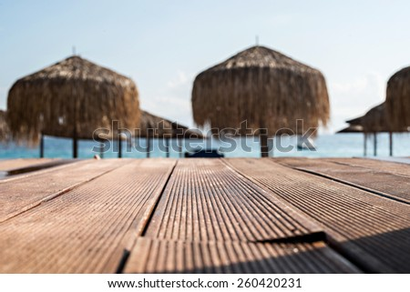 Empty wooden boardwalk with umbrellas on the beach in the background - stock photo