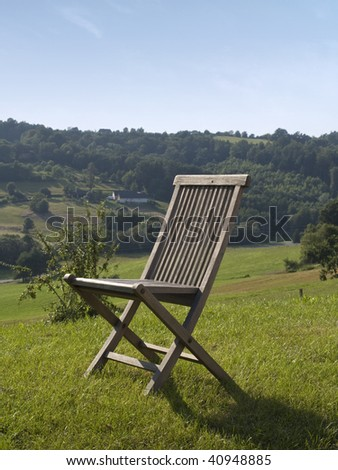 empty wooden chair standing in green grass surrounded by beautiful nature. - stock photo