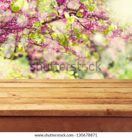 Empty wooden deck table over beautiful spring background - stock photo