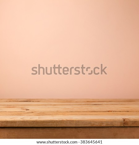 Empty wooden deck table over creamy wallpaper background - stock photo