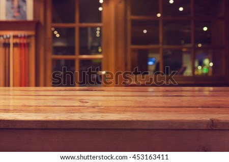 Empty wooden deck table over interior restaurant and bar bokeh background for product montage display  - stock photo