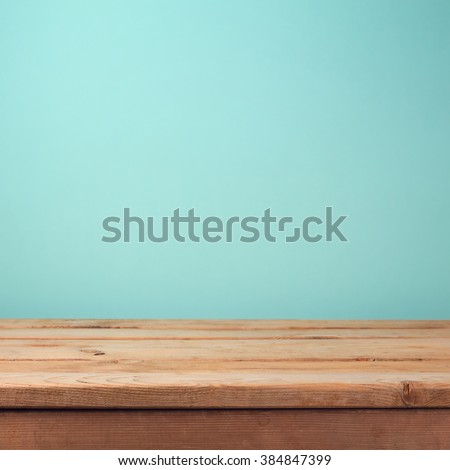Empty wooden deck table over mint wallpaper background - stock photo