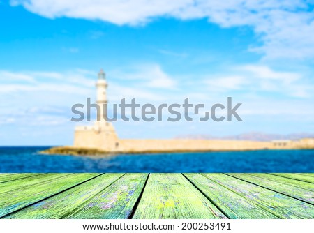 Empty wooden deck table with copyspace and seascape bokeh background. - stock photo