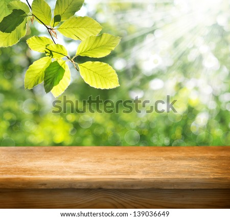 Empty wooden deck table with foliage bokeh background. Ready for product display montage. - stock photo