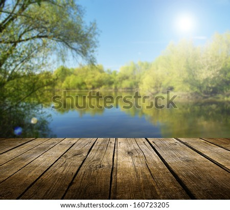Empty wooden deck table with spring lake in background. Ready for product display montage.  - stock photo