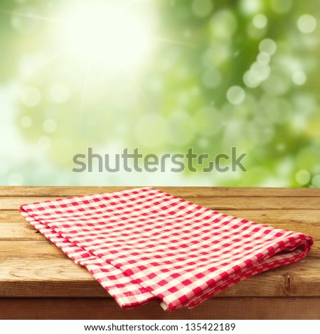 Empty wooden deck table with tablecloth over bokeh background - stock photo