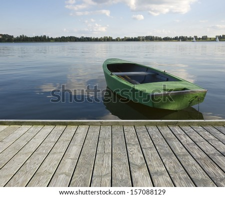 Empty wooden jetty on the lake shore and a boat - stock photo