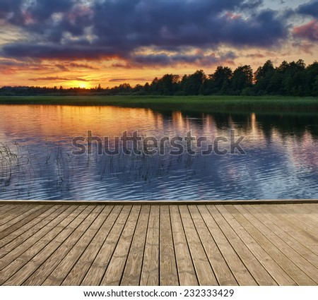 Empty wooden jetty on the lake shore just before sunset, Mazury, Poland - stock photo