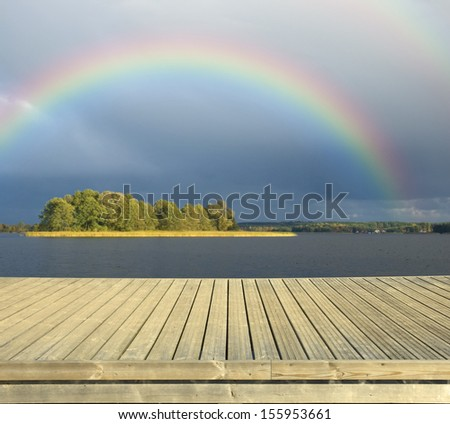 Empty wooden jetty on the lake shore with dark sky and rainbow in the background - stock photo