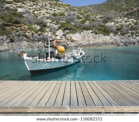 Empty wooden jetty on the seashore with fishing boat in the background - stock photo