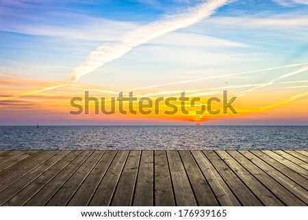 Empty wooden pier at sunrise a beautiful colorful morning. - stock photo