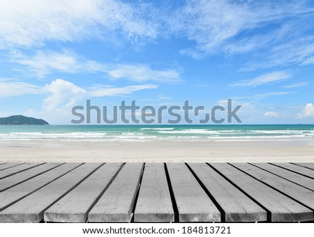 Empty wooden pier beside tropical beach - stock photo