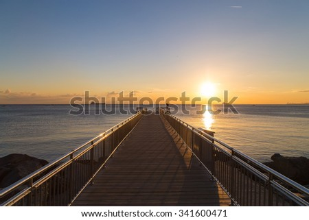 Empty wooden pier during the sunset with reverse light image for design - stock photo