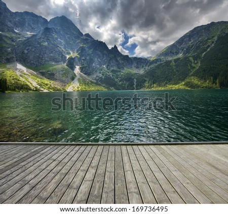 Empty wooden pier with mountain lake in the background - stock photo