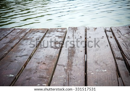 Empty wooden pier with ripple of lagoon water. - stock photo
